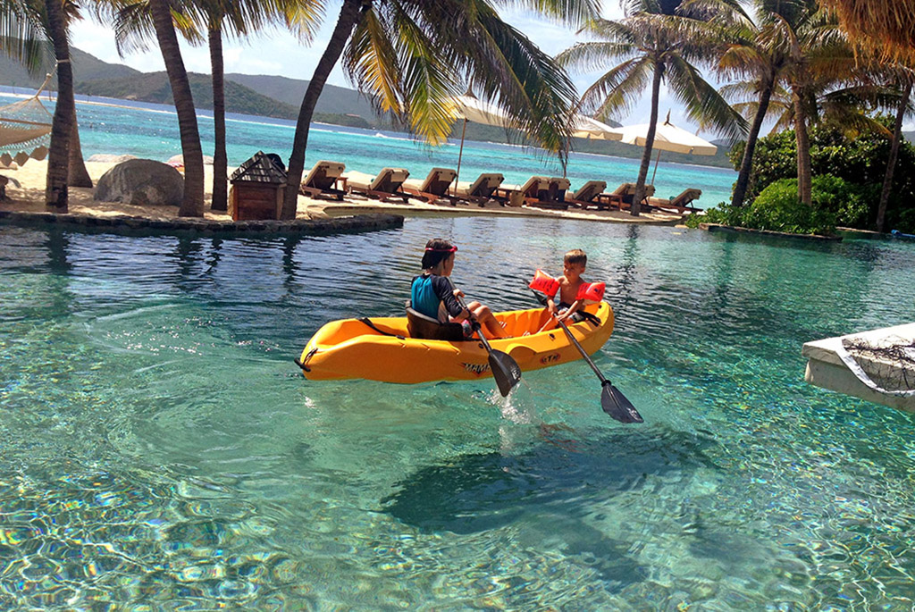 Two children rowing in the Necker Island swimming pool