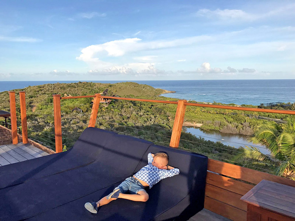 A young boy relaxing on a sun lounger on Necker Island