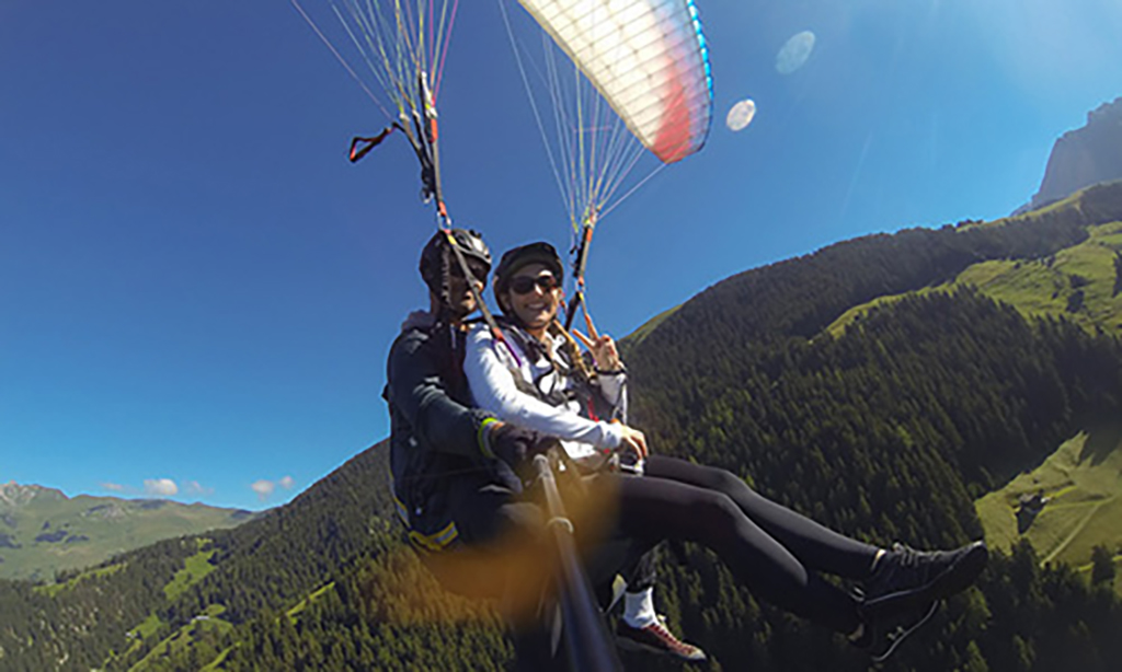 Veronica and her paragliding instructor flying high above Verbier