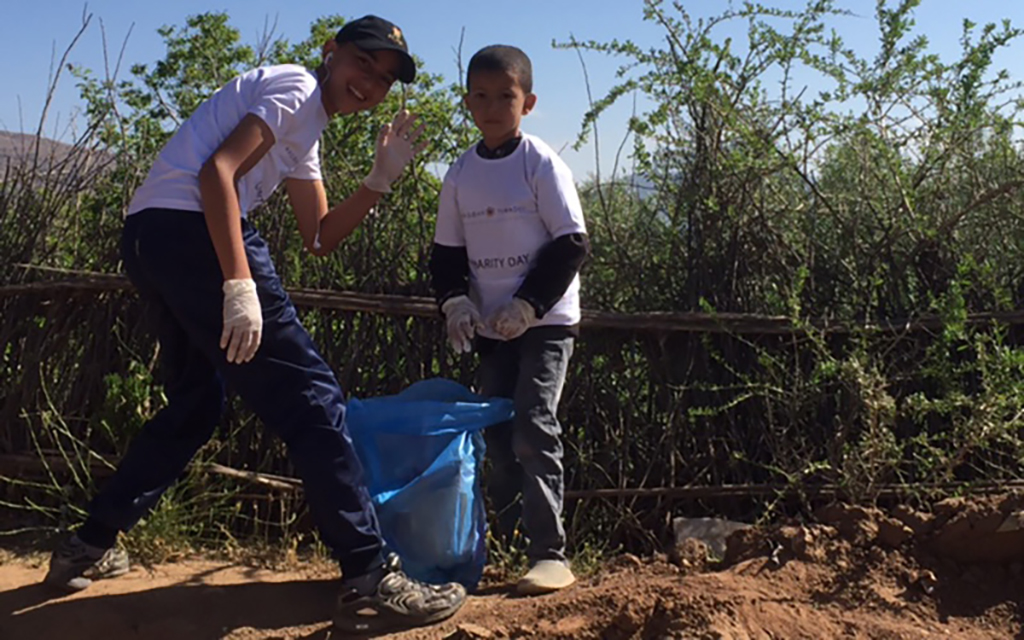 Two boys helping to pick up rubbish