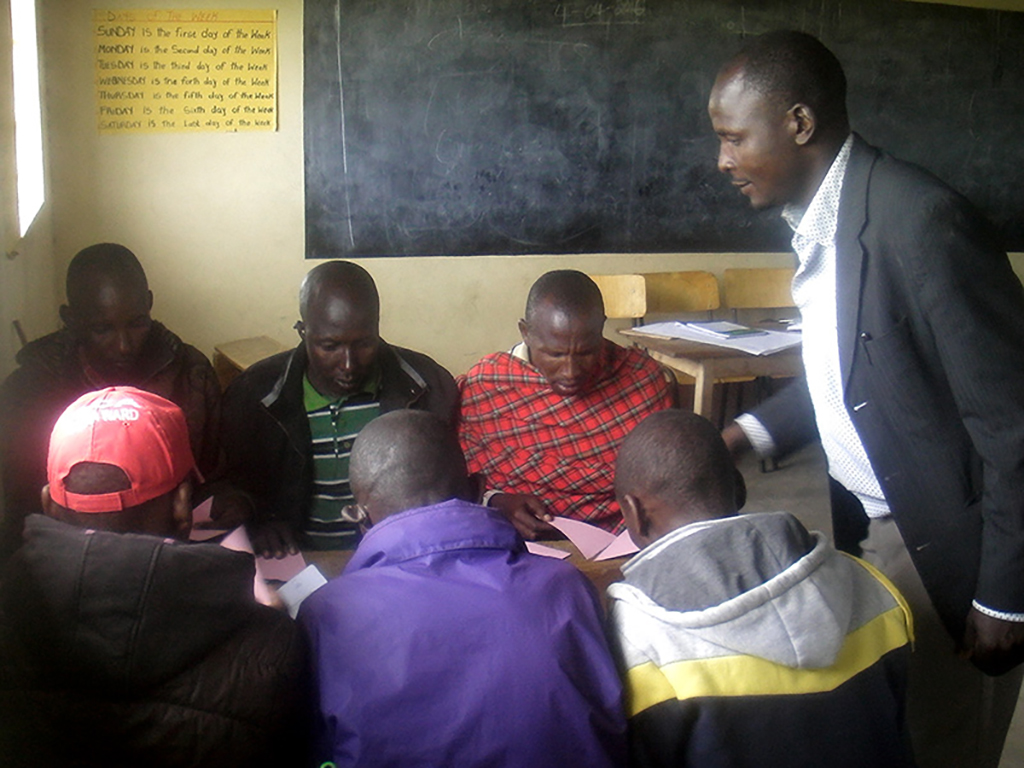Six men sitting and a teacher standing start their training to join the Water Committee