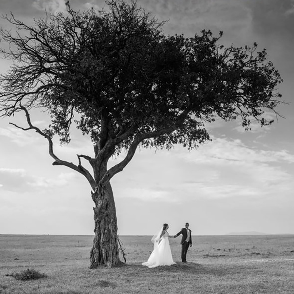 Photography of bride and groom standing under a tree