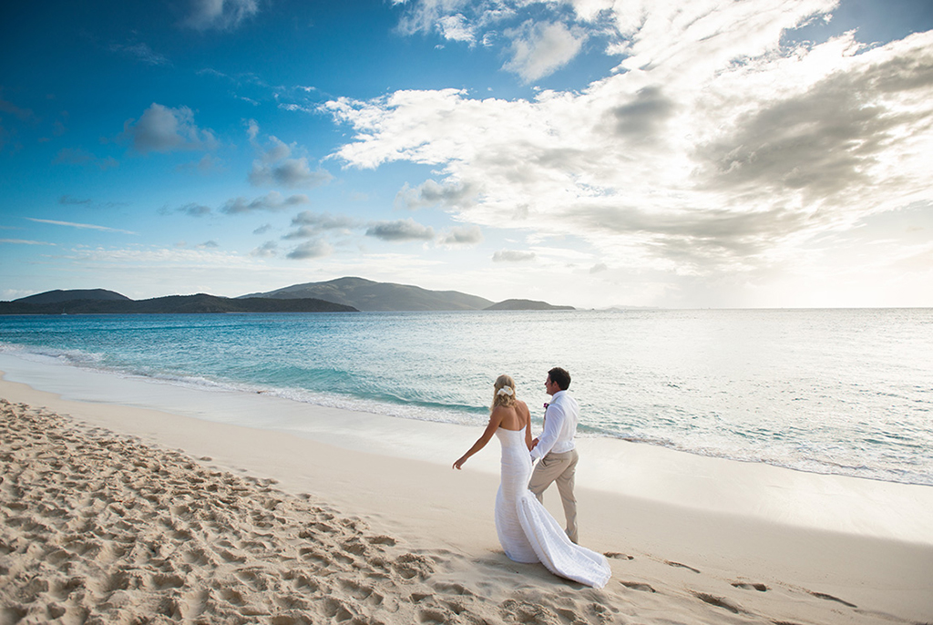 A bride and groom take a stroll on the beack