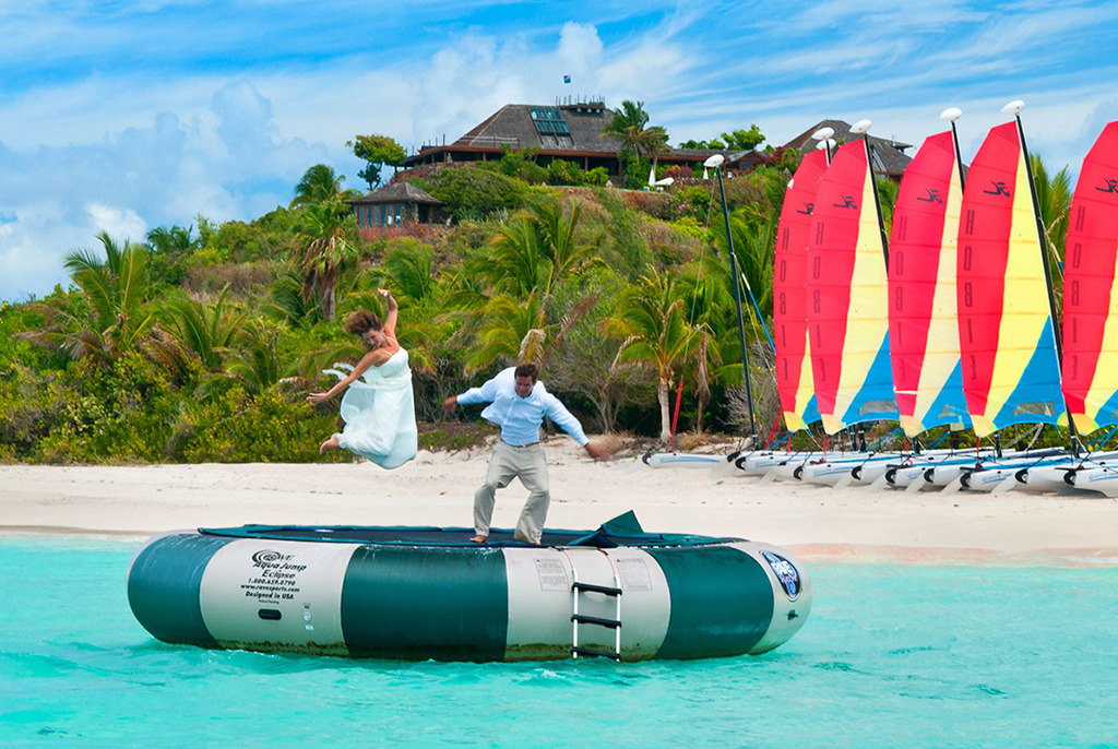 A bride and groom jumping on an inflatable trampoline in the sea on Necker