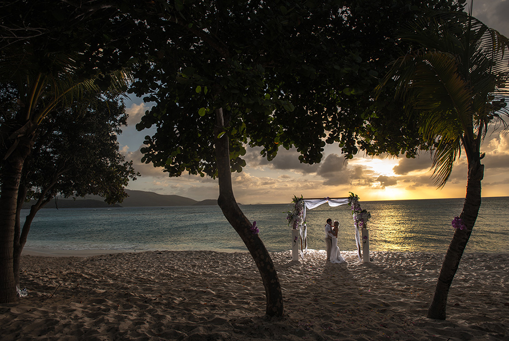 A bride and groom embracing on the beach at sunset
