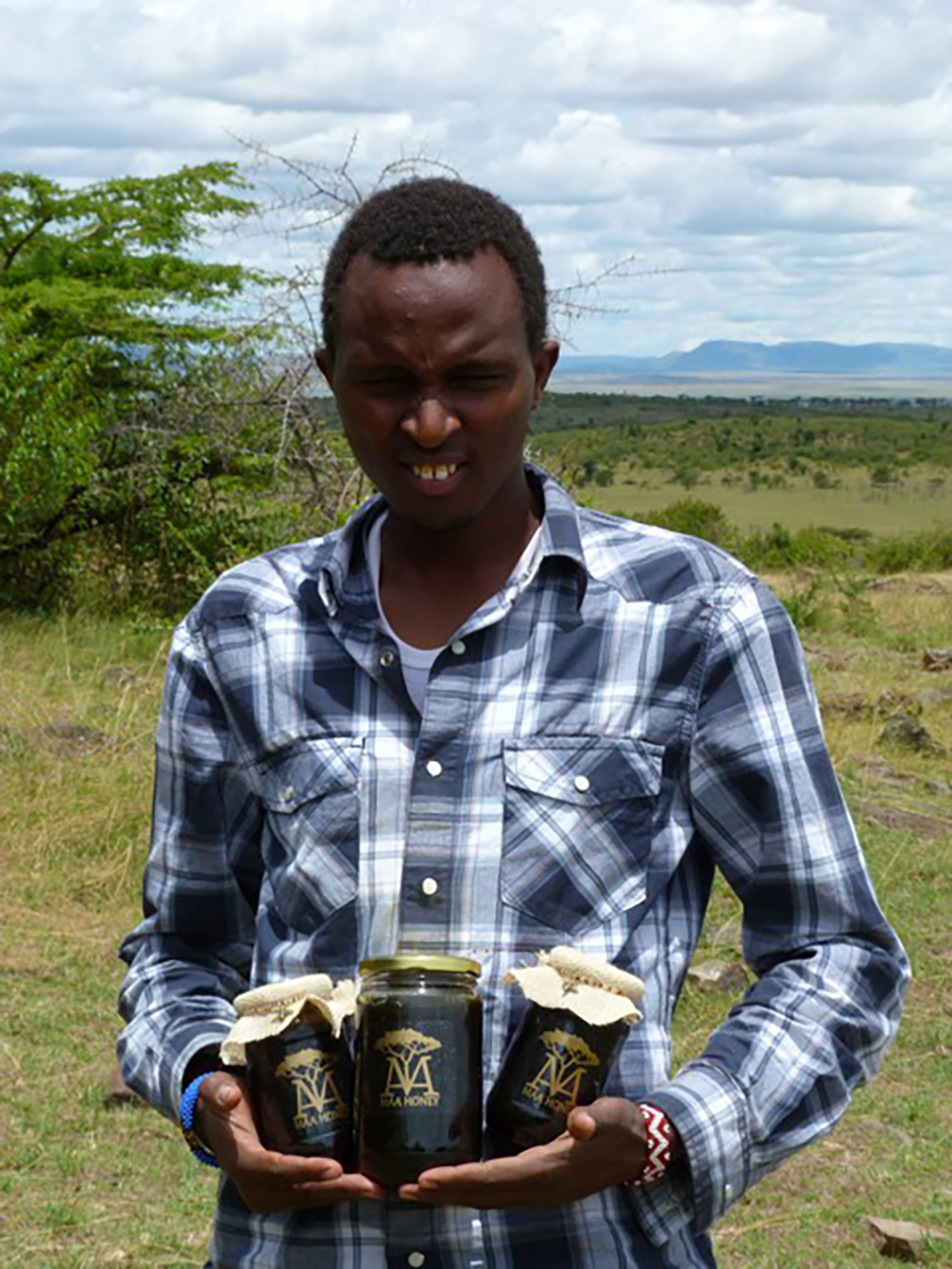 A young man holds three jars of Maa Honey