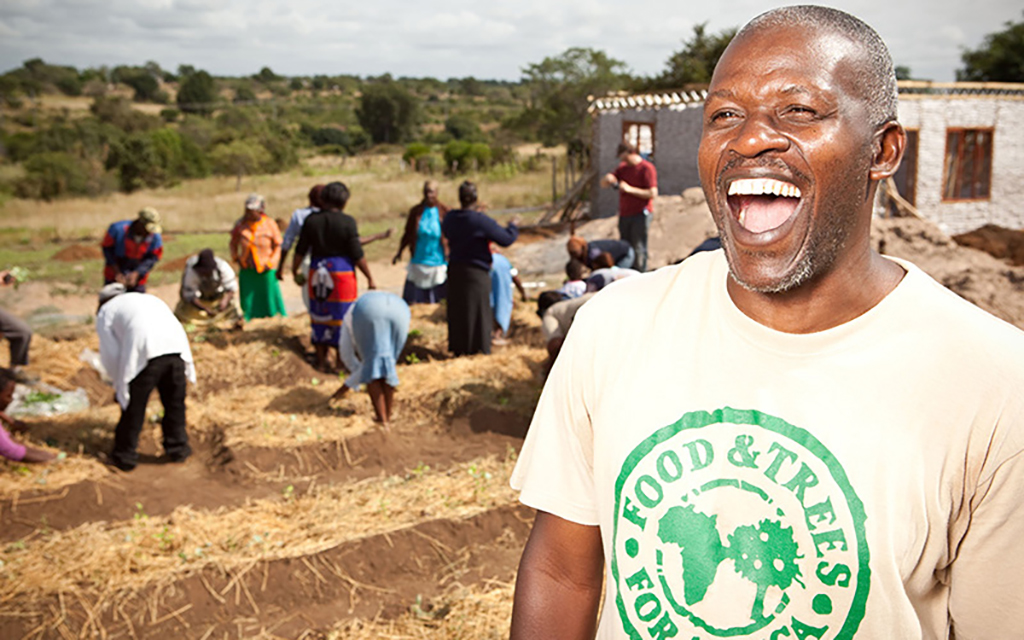 A gentleman laughing in the foreground while other helpers are planting trees in the background