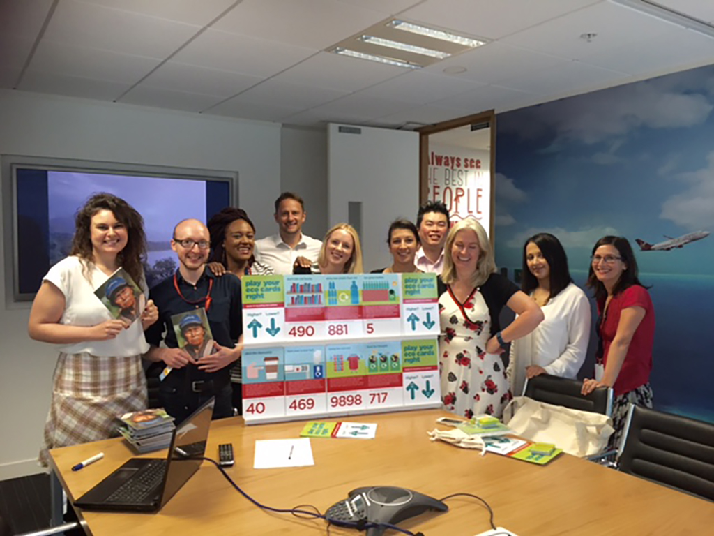 8 team members from Virgin Limited Edition and 2 people from Cool Earth standing next to a board with environmental facts