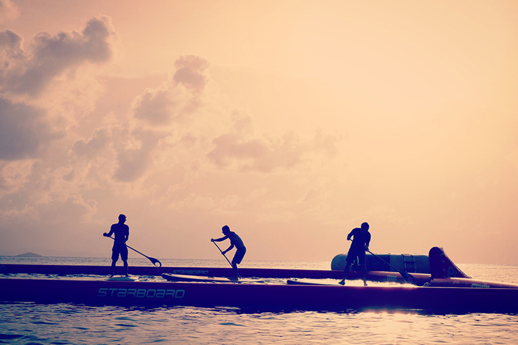 Three people playing Stand Up Paddle Board Water Polo